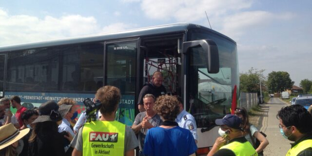 GewerkschafterInnen der FAU und ErntearbeiterInnen vor einem Reisebus